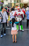 Young girl is photographing a Gundam cosplayer. Royalty Free Stock Images