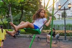 Barnvälfärd. Gullig thailändsk flicka som leker en gunga fotografering för bildbyråer