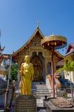 BANGKOK THAILAND, MARS 06, 2018: Den utomhus- sikten av den guld- statyn av en munk på skriva in av en tempel Wat Pho, är en kung Royaltyfria Foton