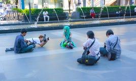 Manfotografer omger det gulliga thailändska Miku lagrar. Arkivbild