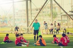Coach training Kid soccer after playing. BANGKOK, THAILAND - MAY 6, 2018 : Kids enjoy training and playing soccer on holiday at TC football club Rama 3 Stock Image