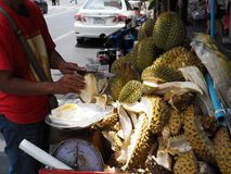 A man uses a knife to cut a durian fruit. BANGKOK, THAILAND - MAY 6, 2018: A man cuts durian fruits on a mobile food cart on May 6, 2018 in Thai capital Bangkok Stock Photo