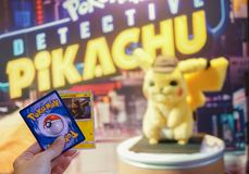 Bangkok, Thailand - May 4, 2019 : A photo of a hand holding Pokemon card game. Pokemon Detective Pikachu movie standee in front of. Theatre to promote movie stock photography