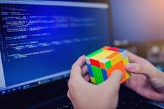 BANGKOK, THAILAND - MAY 15, 2019: Programmer holding Rubik`s cube royalty free stock photography