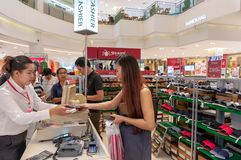 BANGKOK, THAILAND - MAY 20: Unidentified female customer pays for a product purchase at the cashier at a sale in The Mall Bangkhae royalty free stock photography