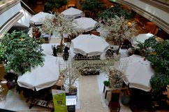 Seating arrangement with umbrellas for upscale French cafe restaurant in shopping mall Bangkok Thailand. Bangkok, Thailand - May 3, 2017: The white elegant Stock Photos