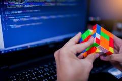 BANGKOK, THAILAND - MEI 15, 2019: De kubus van Rubik van de programmeursholding royalty-vrije stock afbeeldingen