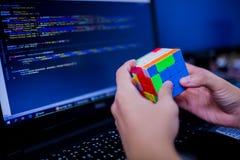BANGKOK, THAILAND - MEI 15, 2019: De kubus van Rubik van de programmeursholding stock afbeelding