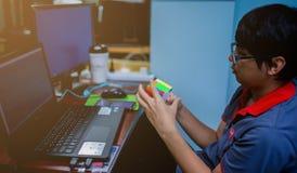 BANGKOK, THAILAND - MEI 15, 2019: De kubus van Rubik van de programmeursholding stock foto's