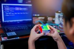 BANGKOK, THAILAND - MEI 15, 2019: De kubus van Rubik van de programmeursholding stock afbeeldingen