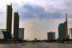 Bangkok, Thailand - Mei 18, 2019: De landschapshorizon bij Chao Pra Ya-rivier met boot, pijler, toren en wolkenkrabbers Bangkok T royalty-vrije stock afbeelding
