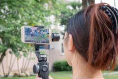 BANGKOK THAILAND - 26 MEI: De naamloze vrouw registreert video gebruikend een Samsung Galaxysmartphone op een Zhiyun gladmaakt gi royalty-vrije stock fotografie