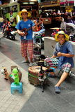 Bangkok, Thailand: Musicians on Silom Road. Two Thai street musicians playing a stringed instrument and drums performing their act on Silom Road in Bangkok royalty free stock images