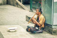 BANGKOK, THAILAND - 21 NOV 2013: Poor man earns his living with. Music on the street Royalty Free Stock Image