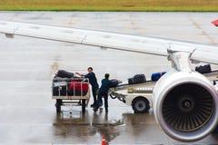 BANGKOK THAILAND - NOVEMBER 28, 2016: Flygplatsarbetare laddar bagage in i nivån kopiera avstånd Royaltyfri Bild