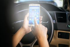 BANGKOK, THAILAND - NOVEMBER 12th, 2017 : Hand of woman using mobile phone with icons of social media on screen in the car Stock Photo