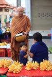 BANGKOK THAILAND - 24. November - thailändischer Mönch, der zur Frau die sitzt in der Front in der Morgenmönchaufgabe, um Lebensmi Stockfotografie