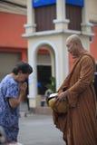 BANGKOK THAILAND - 24. November - thailändischer Mönch, der zur Frau die steht in der Front in der Morgenmönchaufgabe, um Lebensmi Lizenzfreies Stockbild