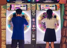 BANGKOK, THAILAND - NOVEMBER 25: Unidentified Couple plays Sega arcade musical game in a sync with each other.  stock images