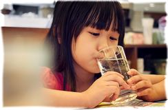 BANGKOK, THAILAND - NOVEMBER 03: A young asian girl takes a sip. From a glass of water in Took Lae Dee restaurant in Bangkok, on Novermber 03, 2017 Royalty Free Stock Photos