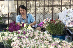 BANGKOK, THAILAND-OCTOBER 26TH 2013: A woman prepares flowers fo Stock Photos