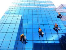 Bangkok, Thailand - October 16, 2017: Group of cleaner hanging, washing and cleaning windows on high rise building stock images