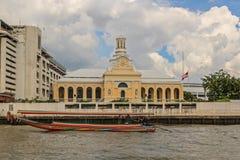 BANGKOK, THAILAND OCTOBER 26 2014:. A long tail boat travels past the historic Royal Seminary on the Chao Phraya River in Bangkok, Thailand royalty free stock photo