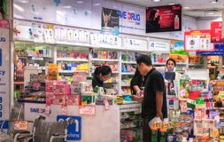 BANGKOK, THAILAND - OCTOBER 28: A Pharmacist in Save Drug Pharmacy located in BigC Extra Petchkasem assists an unidentified stock photography