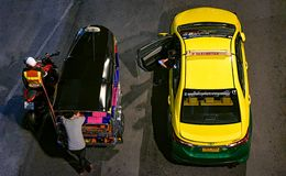 BANGKOK, THAILAND - OCTOBER 20: Taxi and tuktuk drivers park next to each other while waiting for passengers while a policeman pu royalty free stock photography