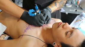 Tattoo artwork at MBK Center Tattoo Fest 2018. BANGKOK, THAILAND - OCTOBER 28, 2018: A Thai artist tattooes a customer at MBK Center Tattoo Fest 2018 on October royalty free stock image