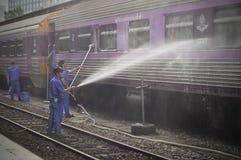 BANGKOK THAILAND - Oktober 2015: Arbetare tvättar drevet på den Bangkok järnvägsstationen (Hua Lamphong i thailändskt språk) Arkivfoto