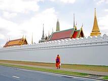 BANGKOK THAILAND - OKTOBER 21, 2016: Munk som går väggen för ` s för kunglig slott för passerande royaltyfria foton