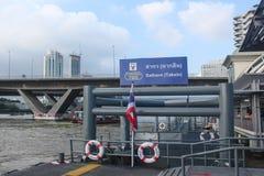 Bangkok Thailand - Oktober 2017: Tom Sathorn pir på anslutningen med BTS Saphan Taksin Thailändsk flagga i pol arkivbild