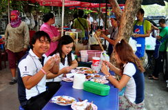 Bangkok, Thailand: People Dining on Sidewalk. A group of Thais eating lunch seated at a sidewalk table set up by local food vendors on Lang Suan Road in Bangkok Stock Photos