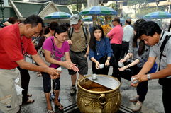 Bangkok, Thailand: People at Erawan Shrine. A group of Thai people washing their hands with holy water before offering their prayers at the Erawan Shrine on Royalty Free Stock Image