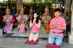 Bangkok, Thailand: People Praying at Erawan Shrine. Thai man and woman praying with women dancers in traditional Thai khong hats and costumes at the revered Stock Photography