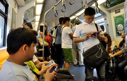Bangkok, Thailand: People Riding on Skytrain. Riders in a train on the Silom Line of the BTS Skytrain system using their ipads and cellphones in Bangkok Stock Photo