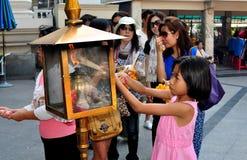 Bangkok Thailand: Pinnar för liten flickaLighing rökelse Royaltyfria Foton