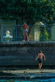 River view of little boys playing at the bay. Children jumping into the water. stock image