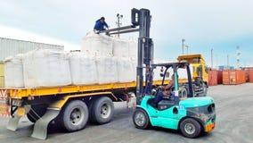 Bangkok, Thailand-16 September 2017: De arbeiders maken jumbozakken van aanhangwagen aan houten korrel leeg bij LCB-containerwerf Stock Foto