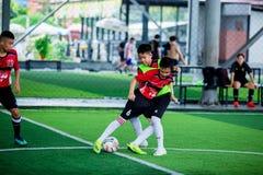 BANGKOK, THAILAND - SEPTEMBER 16, 2018: De jonge geitjes genieten van opleidend en speel voetbal stock afbeeldingen
