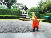 Security guard sitting and wearing orange raincoat to stay alert. Bangkok, Thailand - September 11, 2017: Security guard sitting and wearing orange raincoat to Royalty Free Stock Photo