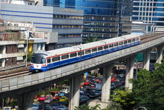 Bangkok, Thailand: Silom Line Skytrain. A BTS Silom Line Skytrain on its elevated track high above the heavy traffic on Sathorn Road enroute from the Surasak to Stock Image