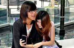 Bangkok, Thailand: Teenage Couple with Cellphone. A teenage girl checks her cell phone sitting with her boy friend in the entrance atrium of the upscale Siam Royalty Free Stock Images