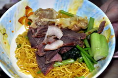 Bangkok, Thailand: Thai-Chinese Pork & Noodles. A classic Thai-Chinese dish of sliced red pork , slices of green onions, and yellow egg Royalty Free Stock Photography