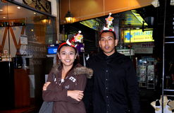 Bangkok, Thailand: Thai Couple Wearing New Year's Hats. Thai couple wearing New Year's Eve hats walking along Sukhamvit Road at Nana in Bangkok, Thailand Stock Photography