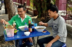 Bangkok, Thailand: Thai Men Eating at Sidewalk Restaurant Royalty Free Stock Image