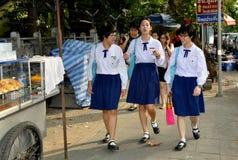 Bangkok, Thailand: Thai School girls. Three Thai school girls wearing their standard uniforms of white blouse and blue skirt walking along Lang Suan Road in Stock Photo