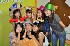 Bangkok, Thailand: Thai Women in Holiday Hats. Seven Thai young women wearing Christmas holiday hats and reindeer antlers posing for friends at the Central World Royalty Free Stock Image
