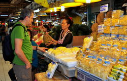 Bangkok, Thailand: Or Tor Kor Market. Thai woman selling a Durian fruit to a westerner at her stand in the daily Or Tor Kor Fresh Food Market in Bangkok Royalty Free Stock Image